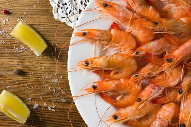 Il piatto con i gamberetti saporiti con il limone sul piatto bianco è servito sulla tavola di vecchio stile con la tovaglia fatta a mano. vista dall'alto Foto Premium