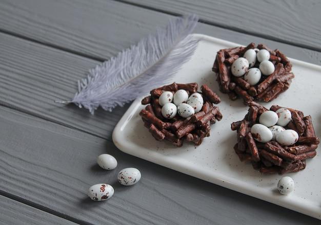 Il piatto dei nidi del cioccolato di primavera ha riempito di uova di pasqua sulla tavola di legno grigia di piuma decorativa grigia. primo piano di concetto dei dolci di pasqua Foto Premium