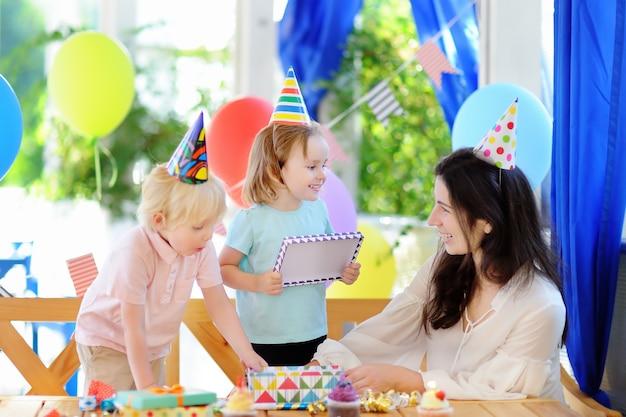 Il piccolo bambino e la loro madre celebrano la festa di compleanno con decorazioni colorate e torte con decorazioni colorate e torta Foto Premium