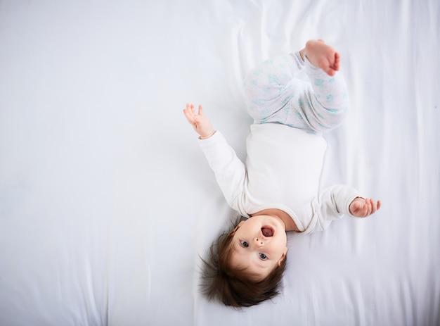 Il piccolo bambino giace sul letto Foto Gratuite
