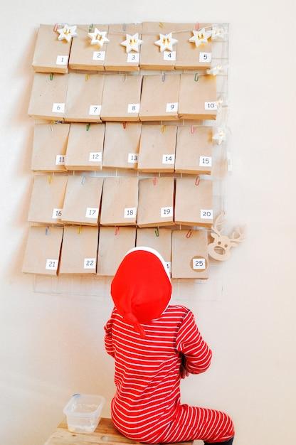 Il piccolo bambino sta aspettando sullo sgabello l'inizio del calendario dell'avvento per natale. Foto Premium