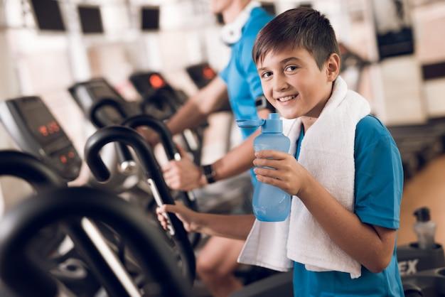 Il piccolo figlio beve l'acqua e sorride alla macchina fotografica. Foto Premium