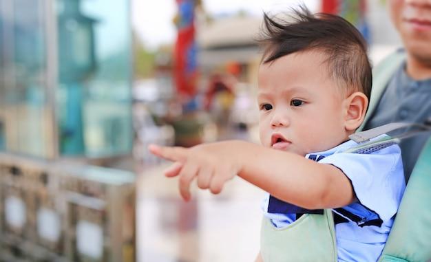 Il piccolo neonato adorabile che indica qualcosa con il padre porta dal hipseat all'aperto. avvicinamento. Foto Premium