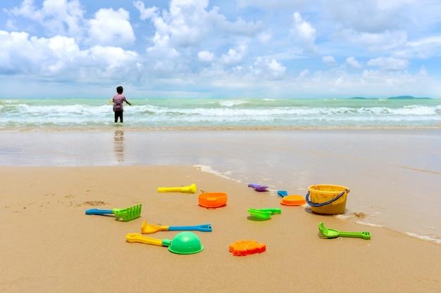 Il piccolo ragazzo asiatico che gioca con la sabbia gioca sulla spiaggia Foto Premium