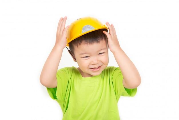 Il piccolo ragazzo asiatico del bambino che gioca i blocchi di legno indossa l'ingegnere del casco Foto Premium