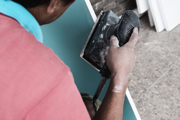 Il pittore sta lavorando al processo di verniciatura della mobilia facendo uso della scrub machine Foto Gratuite