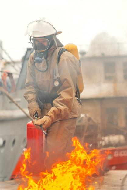 Il pompiere spegne il fuoco con un estintore Foto Premium