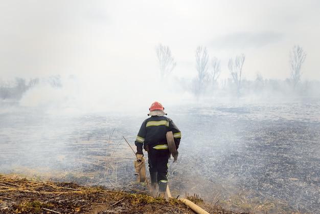 Il pompiere va a spegnere un fuoco naturale Foto Premium