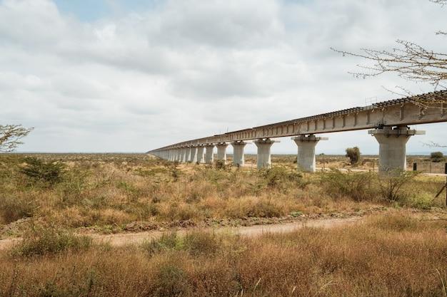 Il ponte lungo sopra un deserto sotto il cielo nuvoloso ha catturato a nairobi, kenya Foto Gratuite