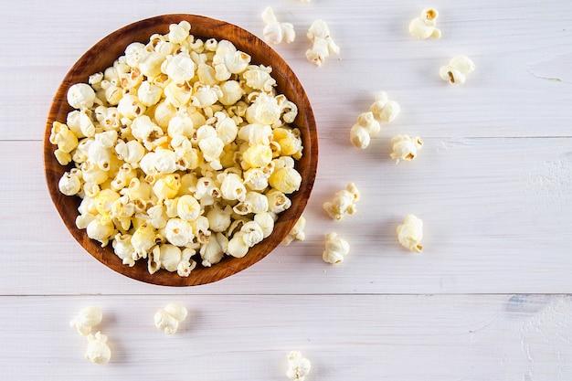 Il popcorn salato in una tazza di legno è su una tavola bianca. il popcorn giace intorno alla ciotola. vista dall'alto. Foto Premium