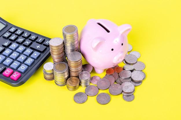 Il porcellino salvadanaio con la pila di moneta e calcolatore sono sulla tavola gialla. risparmio di denaro, concetto finanziario. Foto Premium
