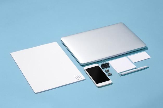 Il portatile, penne, telefono, nota con schermo bianco sul tavolo Foto Gratuite