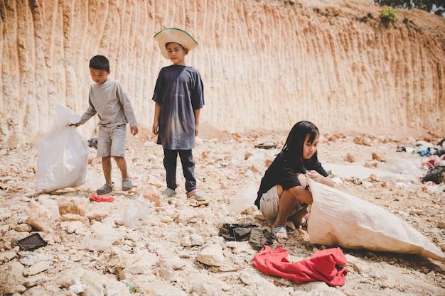 Il povero bambino nella discarica guarda con speranza Foto Gratuite