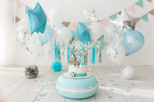 Il primo compleanno ha decorato la stanza con la torta blu che si leva in piedi sul grande maccherone Foto Gratuite