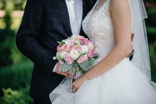 Il primo piano bello e sofisticato del mazzo di nozze tiene la sposa in sue mani vicino allo sposo. bouquet da sposa e anelli. Foto Premium