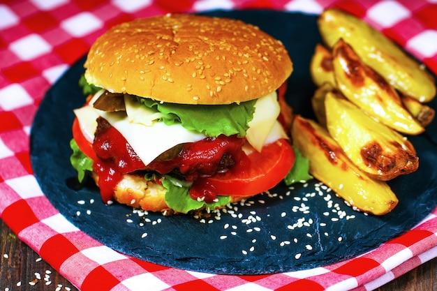 Il primo piano degli hamburger di manzo fatti casa con lattuga è servito sul tagliere e sul tovagliolo di pietra Foto Premium