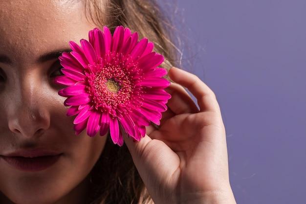 Il primo piano del fiore ha tenuto dallo spazio della copia e della donna Foto Gratuite