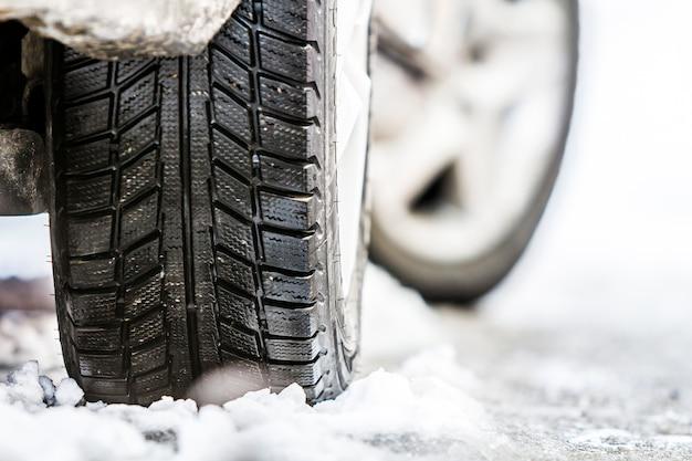 Il primo piano dell'automobile spinge dentro la gomma dell'inverno sulla strada nevosa Foto Premium