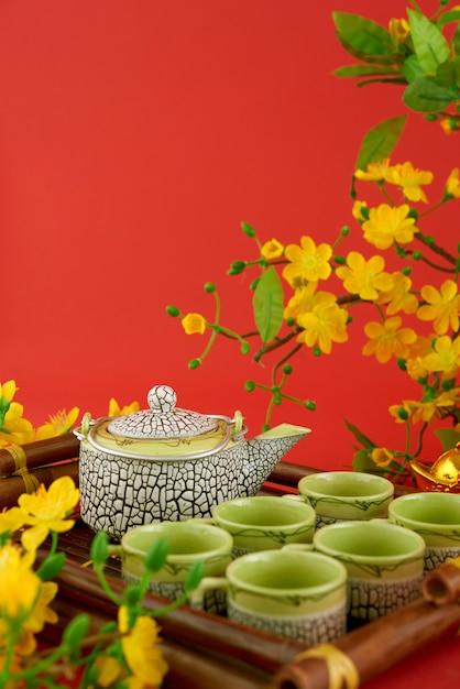 Il primo piano dell'insieme di tè è servito contro fondo e i fiori rossi Foto Gratuite
