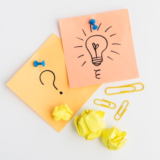 Il primo piano della lampadina tirata e del punto interrogativo firmano sulla nota adesiva allegata con la puntina da disegno blu contro fondo bianco Foto Gratuite