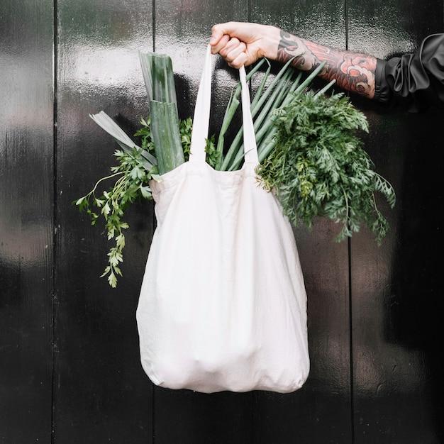 Il primo piano della mano dell'uomo che tiene la borsa di drogheria bianca ha riempito di verdure frondose Foto Gratuite