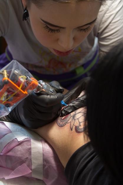 Il primo piano della mano di un maestro del tatuaggio in guanti neri con una macchinetta per tatuaggi fa un tatuaggio secondo lo schizzo Foto Premium