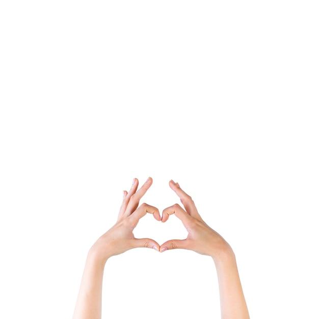 Il primo piano della mano di una donna che fa il cuore modella sopra il contesto bianco Foto Gratuite