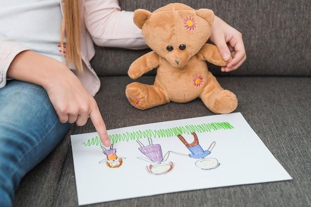 Il primo piano della mano di una ragazza che mostra il disegno della famiglia fatto da lei a orsacchiotto sul sofà Foto Gratuite