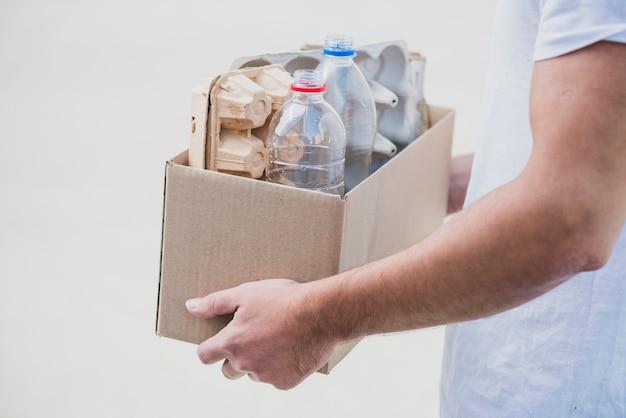 Il primo piano della tenuta della mano ricicla la scatola con il cartone dell'uovo e le bottiglie di plastica sul contesto bianco Foto Gratuite