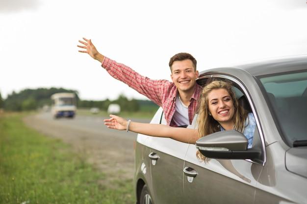 Il primo piano delle coppie sorridenti che ondeggia passa fuori dalla finestra di automobile Foto Gratuite