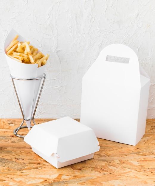 Il primo piano delle patate fritte e del pacchetto dell'alimento deride su sullo scrittorio di legno Foto Gratuite