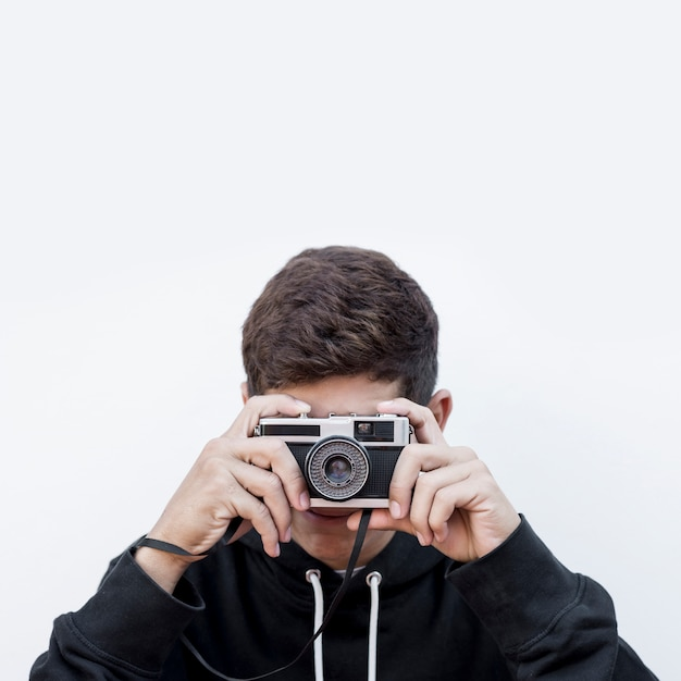 Il primo piano di un adolescente che prende la fotografia clicca sulla retro macchina fotografica d'annata della foto contro fondo bianco Foto Gratuite