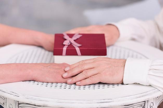 Il primo piano di una coppia che si tiene per mano vicino al contenitore di regalo sulla tavola Foto Gratuite