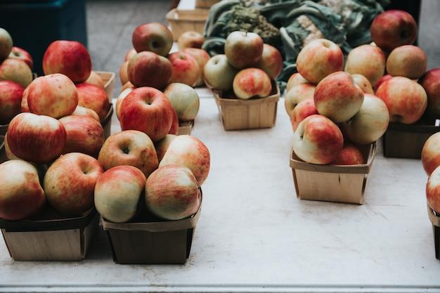 Il primo piano ha sparato delle mele rosse in piccoli canestri nel mercato Foto Gratuite