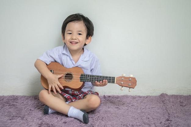 Il primo piano un bambino in ukulele del gioco dell'uniforme dello studente su tappeto con lo spazio della copia Foto Premium