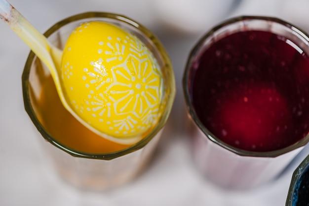 Il processo di dipingere le uova di pasqua con colorante alimentare e cera fusa. pronto. Foto Premium