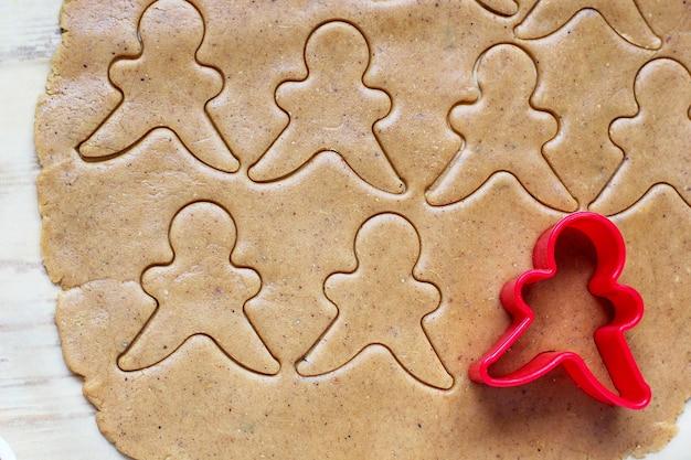 Il processo di gestione dei biscotti dell'uomo di pan di zenzero, usa la pasta di pan di zenzero rossa di taglio della muffa dell'uomo di pan di zenzero su carta da forno intorno alle taglierine variopinte del biscotto sulla tavola di legno bianca. vista dall'alto Foto Gratuite
