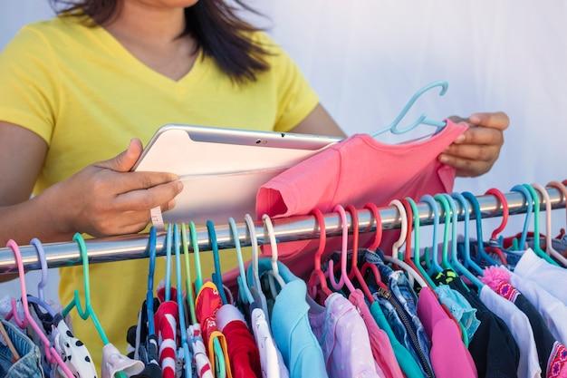 Il proprietario del negozio di abbigliamento per bambini utilizza il tablet per presentare il modello al cliente. Foto Premium