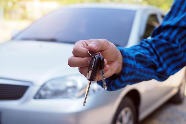 Il proprietario dell'auto è in piedi le chiavi dell'auto per l'acquirente. vendite di auto usate Foto Premium