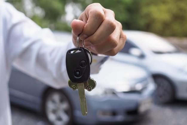 Il proprietario dell'auto è in piedi le chiavi dell'auto per l'acquirente Foto Premium
