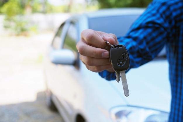 Il proprietario dell'auto è in piedi le chiavi della macchina per l'acquirente. Foto Premium