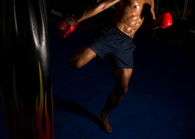 Il pugile calcia all'obiettivo sul ring in palestra Foto Premium