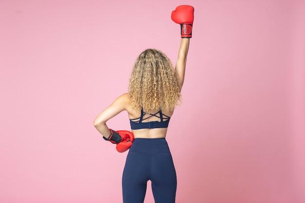 Il pugile grazioso della donna dai capelli biondi e vestito in abiti sportivi sta sorridendo felicemente su un isolato di due colori rosa e gialli Foto Premium