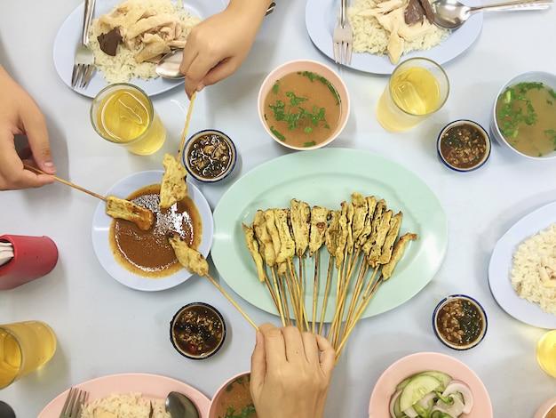 Il punto di vista superiore del pranzo della famiglia include l'insieme del riso del pollo e il bastone satay del porco - concetto felice del pasto di vista superiore asiatica Foto Gratuite