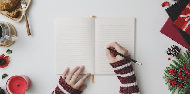 Il punto di vista superiore di scrittura della giovane donna sul taccuino nel natale ha decorato il posto di lavoro Foto Premium