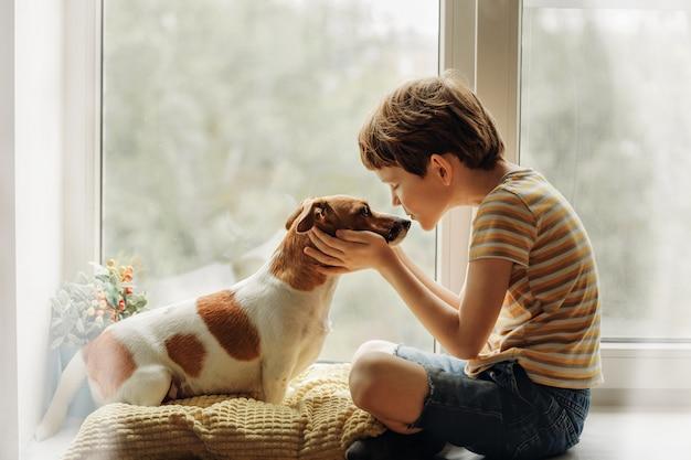 Il ragazzino bacia il cane nel naso sulla finestra. Foto Premium