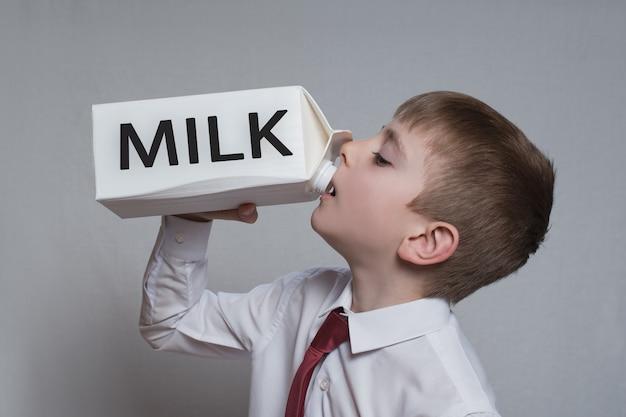 Il ragazzino beve da un grande pacchetto di latte bianco. camicia bianca e cravatta rossa. Foto Premium