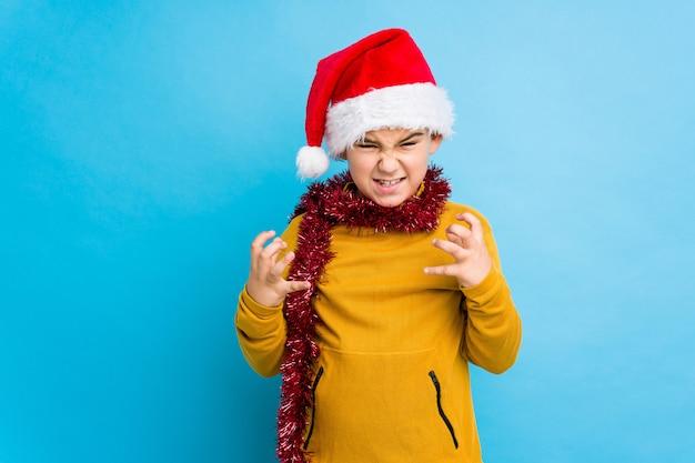Il ragazzino che celebra il giorno di natale che porta un cappello di santa ha isolato il ribaltamento che grida con le mani tese. Foto Premium