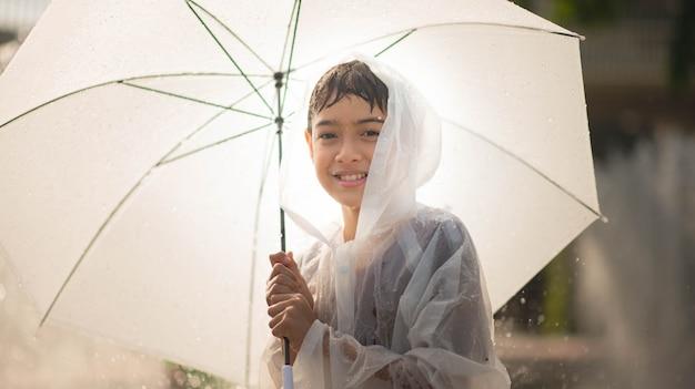 Il ragazzino che gioca l'acqua cade la fontana sotto il panno e l'ombrello Foto Premium
