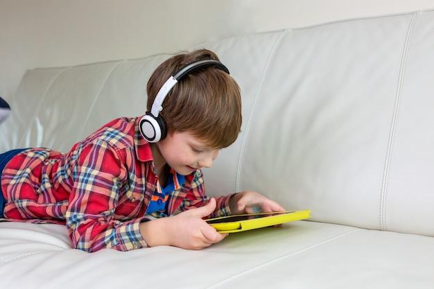Il ragazzino che pone sul letto gioca il ridurre in pani Foto Premium
